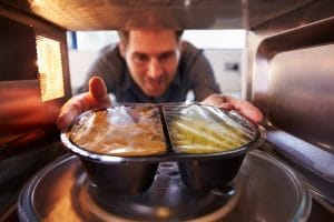 Man Putting Dinner Into Microwave